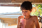 Boy drinking milkshake cocktail on beach
