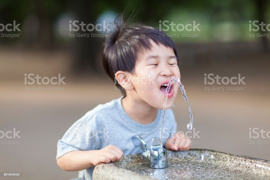Boy Drinking Water From Water Fountain stock photo