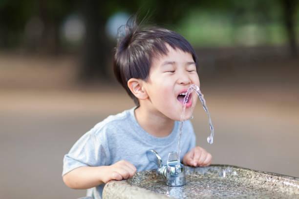 eau potable garçon de fontaine d'eau - fontaine photos et images de collection