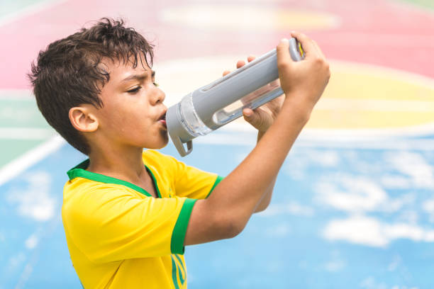 Boy drinking water on court Child, Drinking, Drinking Water, Water, Sport groyne stock pictures, royalty-free photos & images
