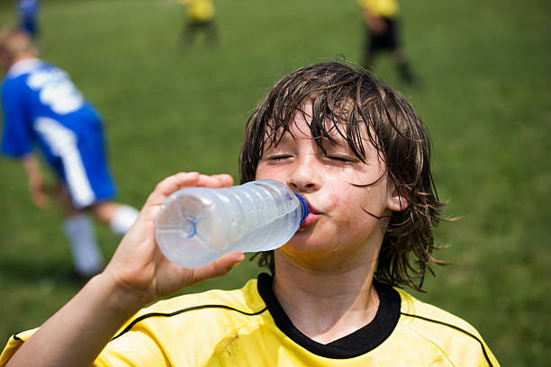 boy drinking water Thirsty soccer player drinking water on the sidelines of playing field. groyne stock pictures, royalty-free photos & images