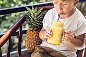 A boy drinks a pineapple smoothie on the terrace.