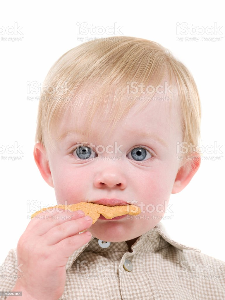Boy eating a biscuit 免版稅 stock photo