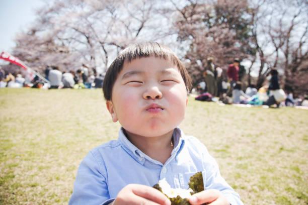 公園でご飯を食べる少年 - 子供時代 ストックフォトと画像