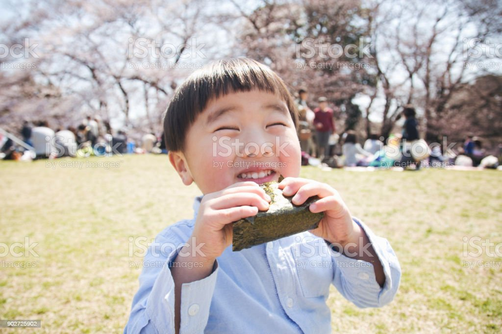 Boy eating a rice bowl in the park - foto stock