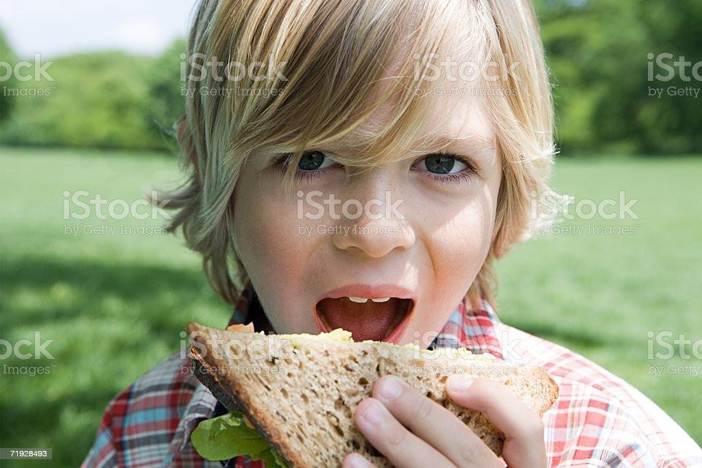 Menino comer uma sanduíche foto de stock royalty-free