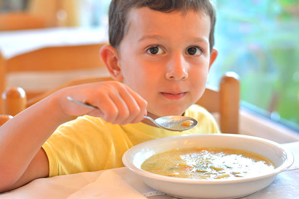 Boy Eating a Soup in Restaurant – Foto