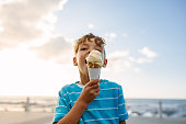 Boy eating an ice cream standing near seafront. Little boy on vacation treating himself to an ice cream.