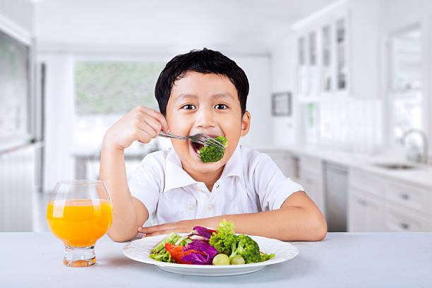 junge essen brokkoli wie zu hause fühlen. - innocent saft stock-fotos und bilder