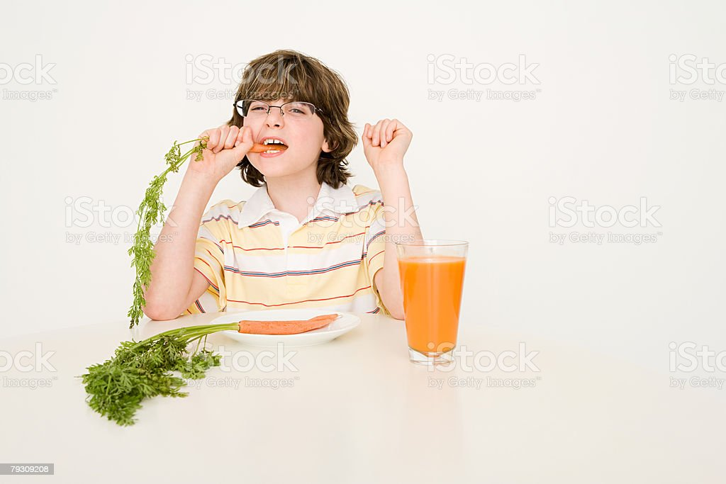 A boy eating carrots 免版稅 stock photo