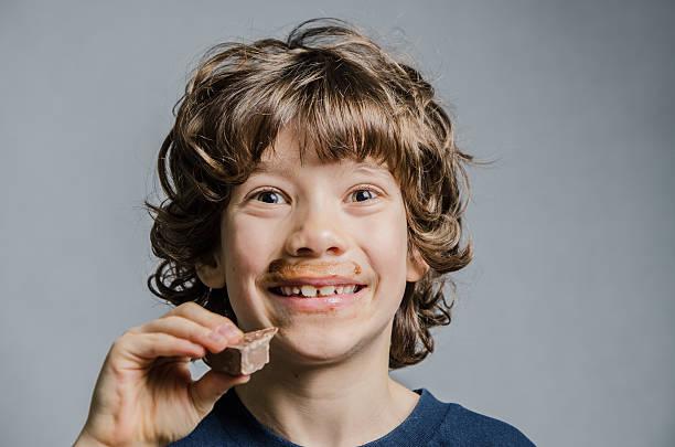 menino comer o chocolate e chocolate em torno da boca - boca suja imagens e fotografias de stock