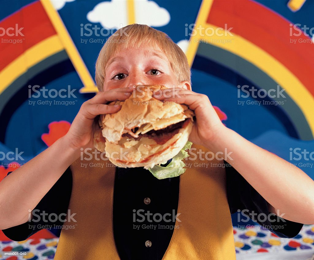 Boy eating hamburger royalty-free stock photo