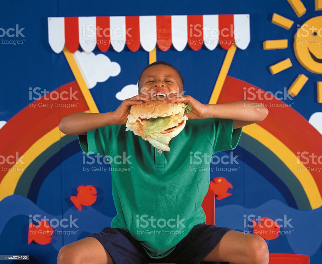 Boy eating hamburger 免版稅 stock photo