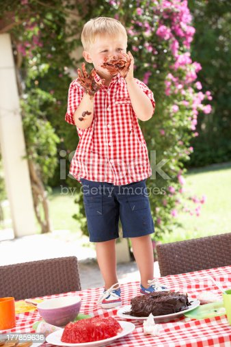 Boy Eating Jelly And Cake At Outdoor Tea Party Being Messy Standing On Table