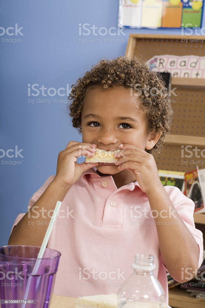 Boy (4-5) eating lunch in classroom foto de stock libre de derechos