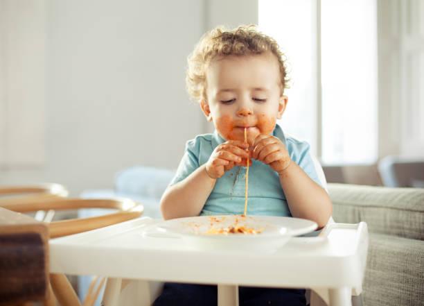junge essen-pasta - spaghetti tomatensauce stock-fotos und bilder