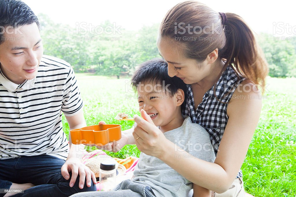 Boy eating rice happily a park stock photo