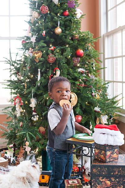 ragazzo mangiando santa di cookie - santa claus tiptoeing foto e immagini stock