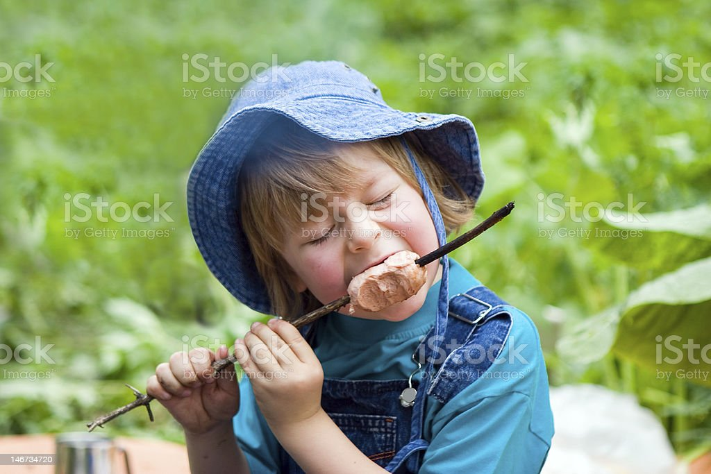 Boy eating sausage cooking by bonfire in hike (series children) stock photo