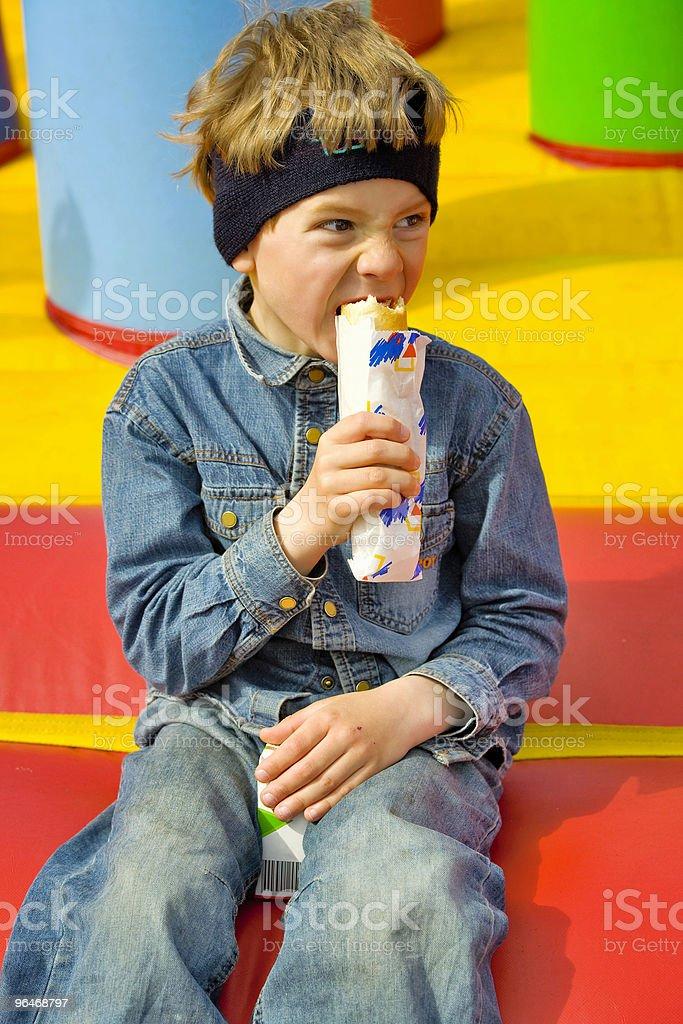 Boy eats hot dog royalty-free stock photo