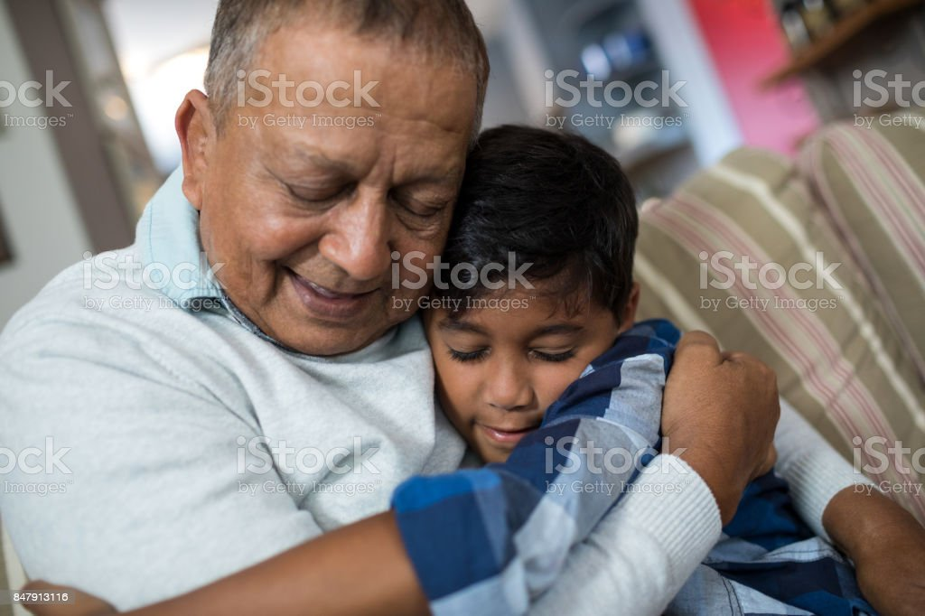 Boy embracing grandfather stock photo