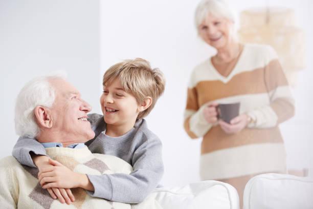 junge umarmen seines großvaters - emoticon hug stock-fotos und bilder