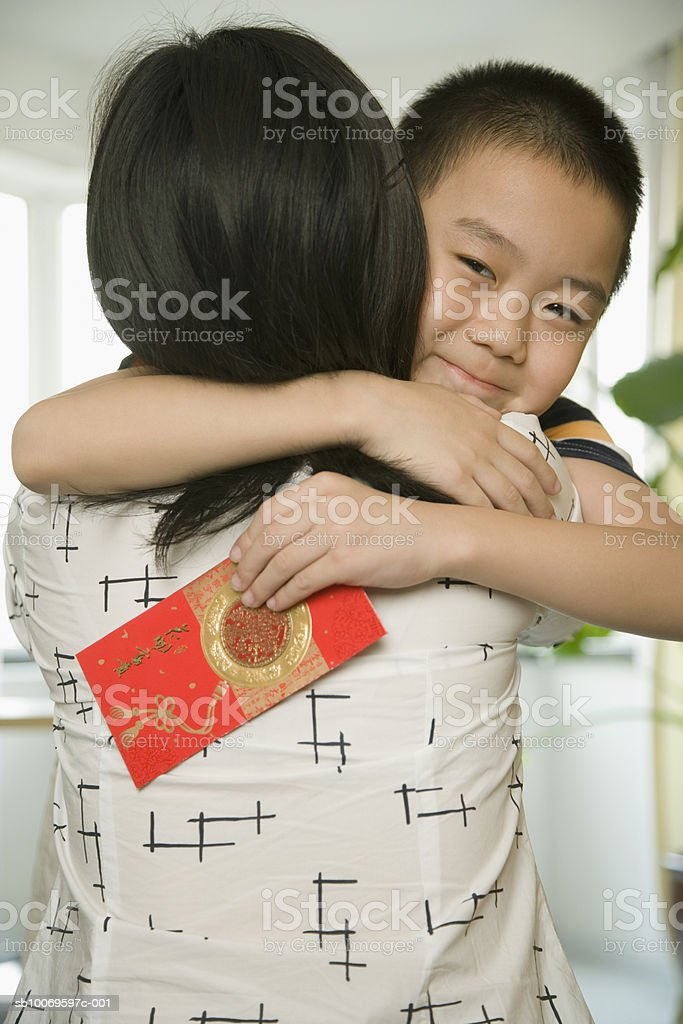 Boy (8-9) embracing mother Lizenzfreies stock-foto