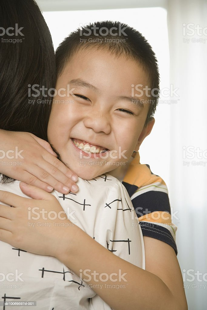 Boy (8-9) embracing mother foto de stock libre de derechos