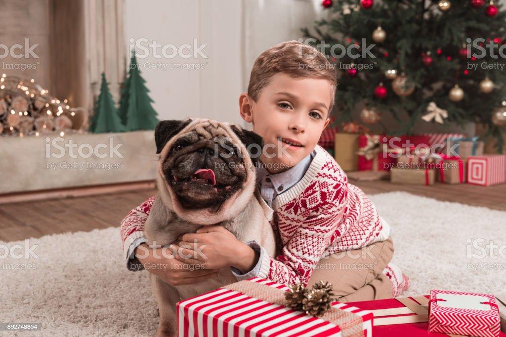 boy embracing pug on christmas stock photo