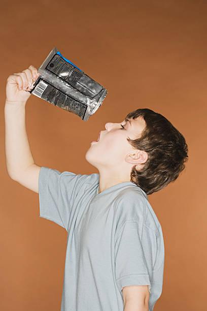junge emptying frischen paket in den mund - kinder verpackung stock-fotos und bilder