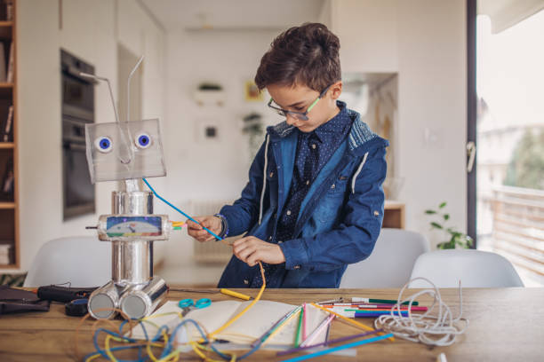 Boy engineer making a robot at home One boy, making a robot from recycled materials, working on creative homework at home. stem topic stock pictures, royalty-free photos & images