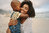 Son kissing his mother at the sea shore. Boy enjoying at day out with his mother on the beach.