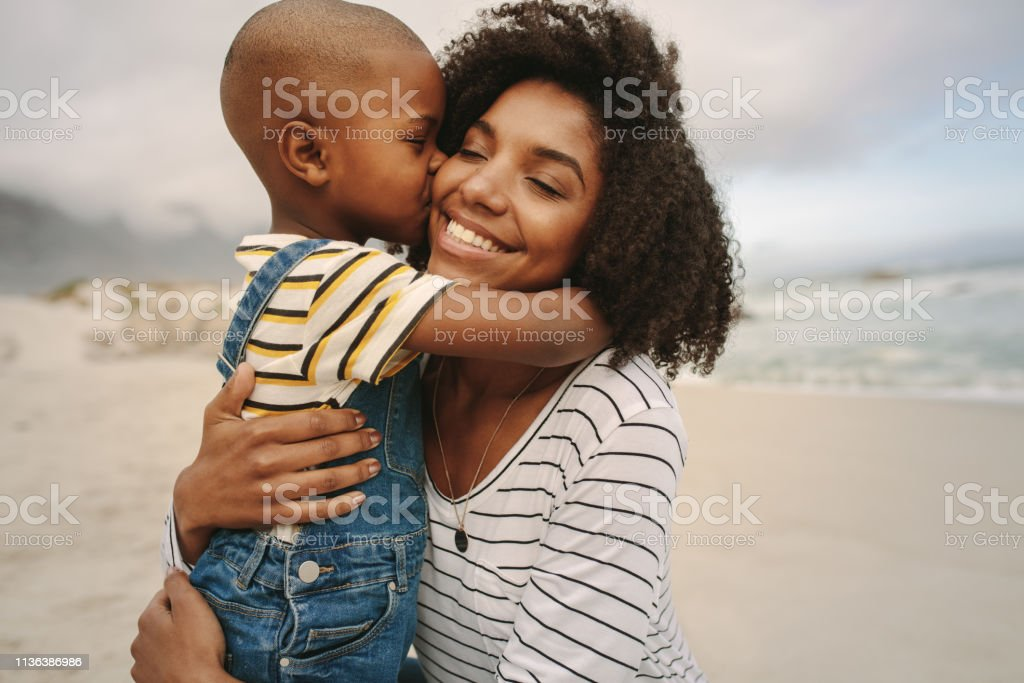 Boy enjoying at day out with his mother on the beach stock photo