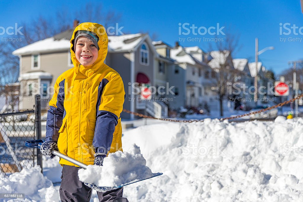 boy enjoys the snow removal stock photo