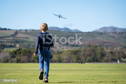 A young boy has fun throwing his foam plane on an open field in the countryside. Young schoolboy has fun playing at the public park