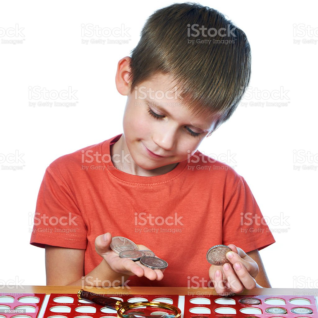 Boy examines coins from his collection isolated stock photo