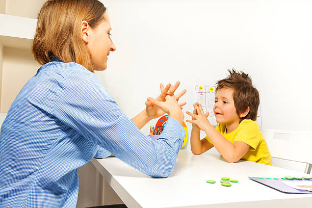 boy exercises putting fingers with therapist - autism stock photos and pictures