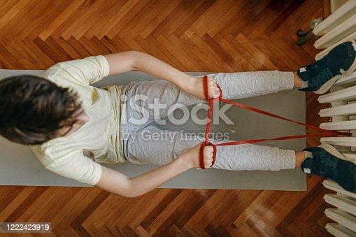 Boy doing stretching exercise with resistance band at home