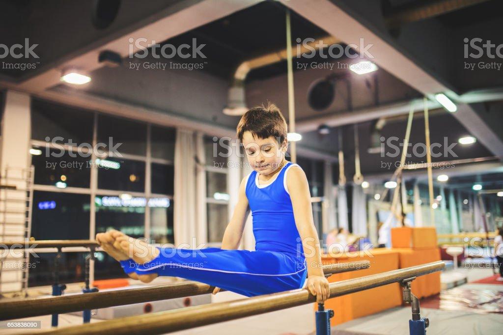 Boy exercising on parallel bars. stock photo