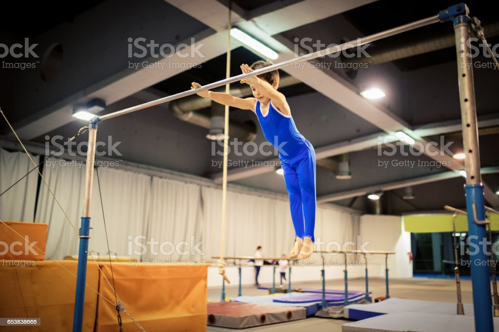 Boy exercising on uneven parallel bars stock photo