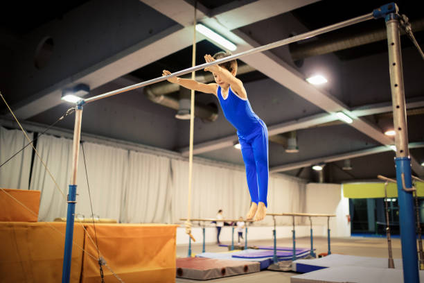 boy exercising on uneven parallel bars - uneven parallel bars stock photos and pictures