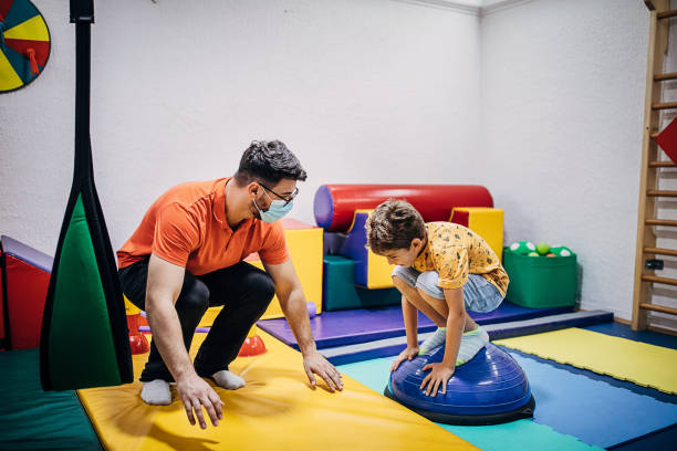 Boy exercising with physical therapist in sensory room stock photo
