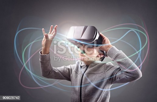 istock Boy experiencing using a virtual reality headset 909025742