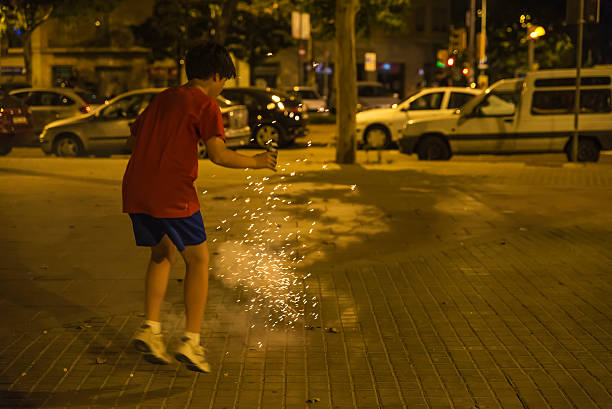 boy exploding firecrackers, barcelona - petard stock photos and pictures