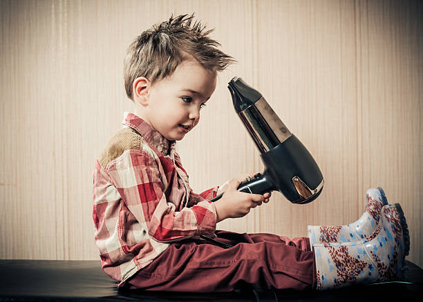 boy exploring hairdryer stock photo