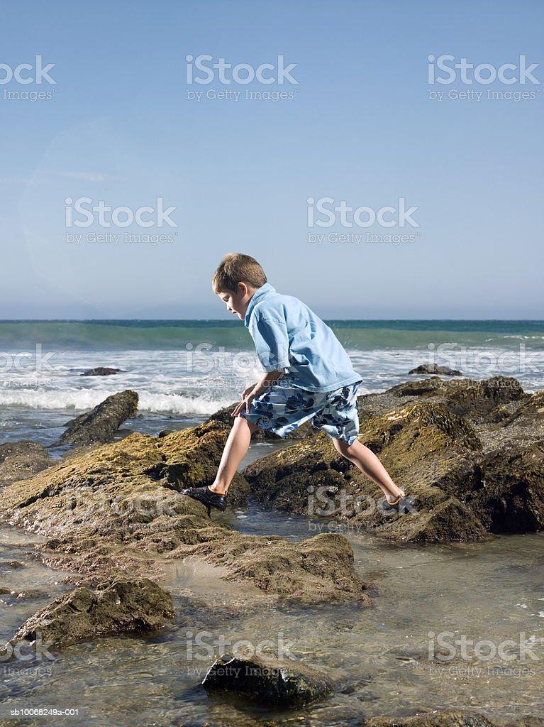 Menino (6 a 7) explorando a costa foto royalty-free