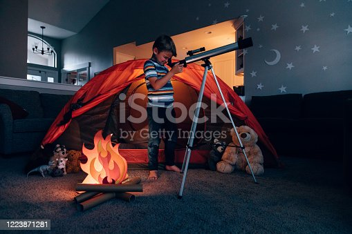 A boy in his home searches for stars through his telescope due to the coronavirus restrictions and quarantine. His tent is pitched in the living room of the home along with stuffed animal friends and have a fake campfire next to a telescope. He is searching the skies for stars and dreams and looking forward to safely returning outdoors.