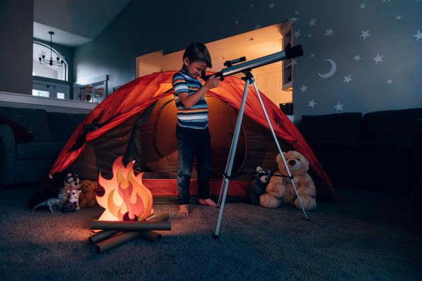 Boy Exploring with Telescope Indoors stock photo