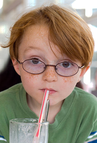 boy & eye glasses, child drinking chocolate milk shake at restaurant - nerd boy eating stock photos and pictures