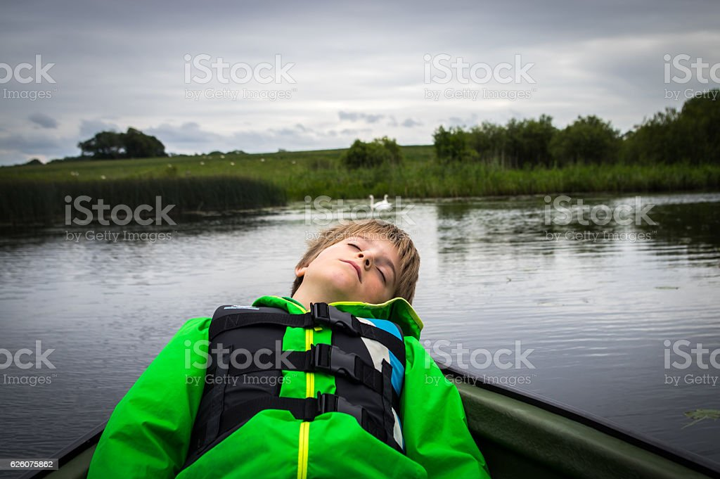 Boy, eyes closed, resting in small boat on lake stock photo